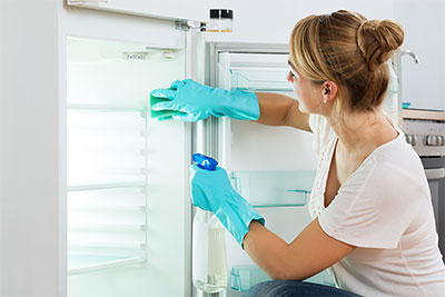 Woman cleaning fridge - Cleaning tips for moving