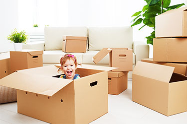 Toddler with moving boxes - Moving tips for parents