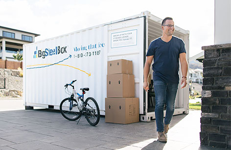 Man loading a moving container in driveway - BigSteelBox